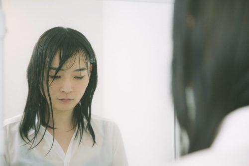 雨の日に傘をささずに濡れる女性